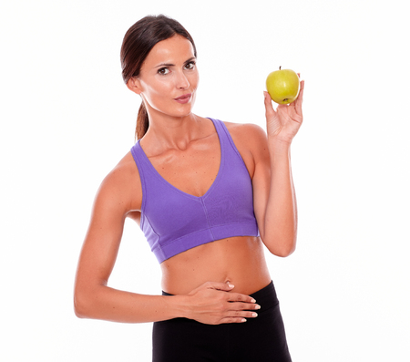 hair tied back: Healthy smiling brunette with apple looking at camera and a hand on her waist, wearing violet and black gymnastic clothing, her hair tied back, isolated