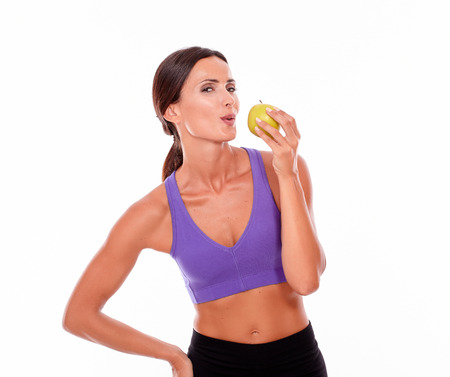 hair tied back: Healthy pouting brunette with apple looking at camera, hand on hip while wearing violet and black gymnastic clothing and her hair tied back isolated Stock Photo