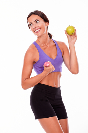 hair tied: In shape woman lifting pink weight, holding an apple, looking away while wearing violet and black gymnastic clothing and her hair tied back isolated