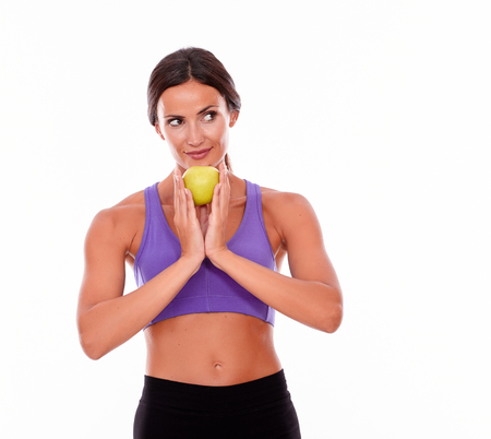 hair tied back: Healthy smiling brunette looking away secretively while holding apple to her chin, wearing violet and black gymnastic clothing with her hair tied back, isolated