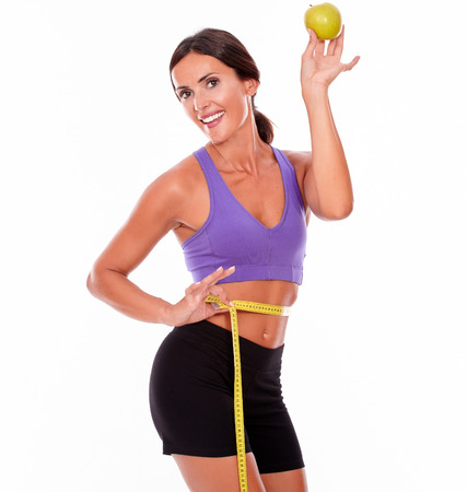 hair tied back: Healthy smiling brunette holding apple looking at camera, measuring her waist while wearing violet and black gymnastic clothing and her hair tied back isolated Stock Photo