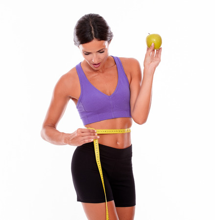 hair tied back: Healthy woman holding apple looking at tape measure while measuring her waist wearing violet and black gymnastic clothing and her hair tied back isolated Stock Photo
