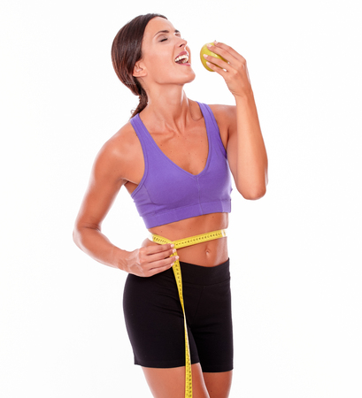 hair tied back: Healthy smiling brunette holding apple to mouth with eyes closed, measuring her waist while wearing violet and black gymnastic clothing, her hair tied back isolated Stock Photo