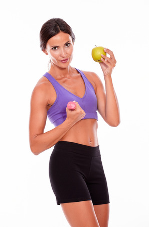hair tied back: In shape woman lifting pink weight, holding an apple, looking at camera while wearing violet and black gymnastic clothing and her hair tied back isolated
