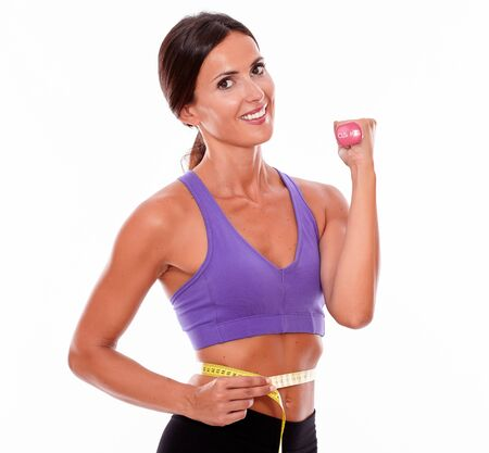 hair tied back: In shape woman lifting weight, looking at camera, smiling, while measuring her waist wearing violet and black gymnastic clothing and her hair tied back, isolated Stock Photo