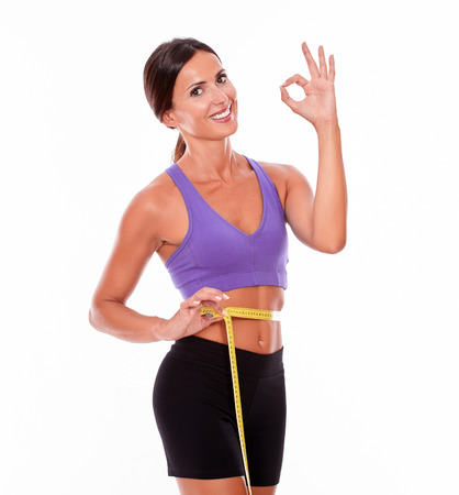perfect sign: Beautiful brunette gesturing perfect sign, looking at camera, smiling while measuring her waist wearing violet and black gymnastic clothing and her hair tied back, isolated