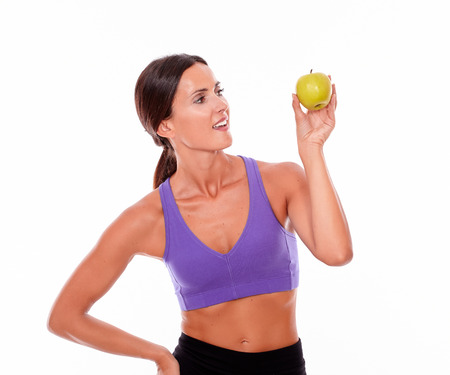 hair tied back: Healthy smiling brunette looking at apple with a toothy smile, hand on hip, wearing violet and black gymnastic clothing, her long hair tied back isolated