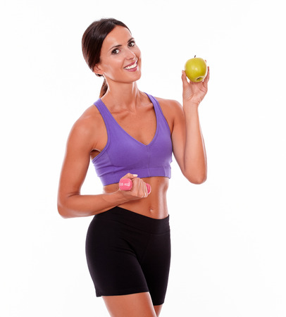 hair tied back: Happy smiling brunette holding an apple and pink weight looking at camera while wearing violet and black gymnastic clothing and her hair tied back isolated Stock Photo