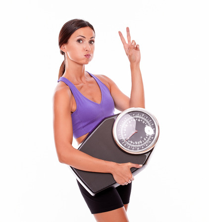 hair tied: Healthy pouting brunette woman with a scale, gesturing a peace sign while wearing her hair tied back and violet and black gymnastic clothing, isolated Stock Photo
