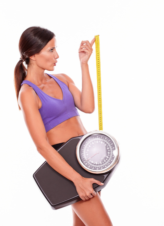hair tied back: Healthy pouting brunette woman with a tape measure and a scale looking away while wearing violet and black gymnastic clothing, hair tied back, isolated