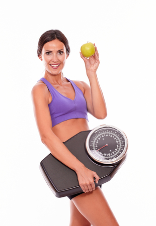 hair tied back: Healthy brunette woman with a scale and green apple smiling while looking at the camera with violet and black gymnastic clothing, hair tied back, isolated