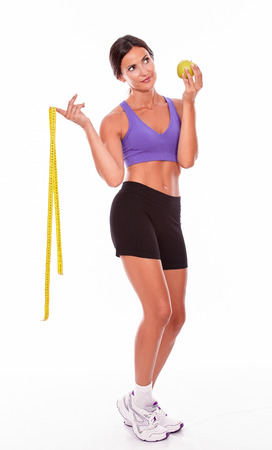 hair tied back: Healthy brunette woman with a tape measure and apple thoughtfully looking away while wearing gymnastic clothing, hair tied back, isolated