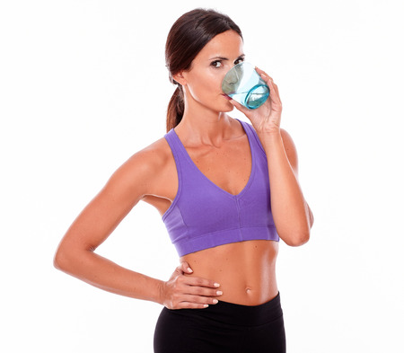 hair tied back: Healthy young brunette woman drinking a glass of water while wearing violet and black gymnastic clothing, hand on hip, hair tied back, isolated Stock Photo