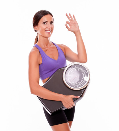 perfect sign: Healthy smiling brunette woman with a scale, gesturing a perfect sign while wearing her hair tied back and violet and black gymnastic clothing, isolated Stock Photo