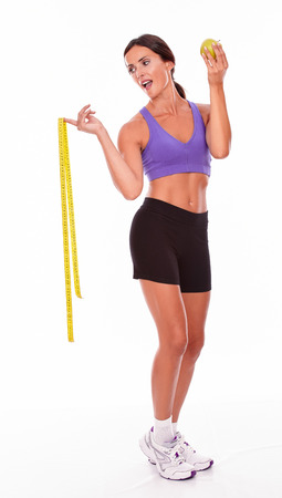hair tied back: Healthy brunette woman with a green apple smiling while looking at tape measure wearing violet and black gymnastic clothing, hair tied back, isolated Stock Photo