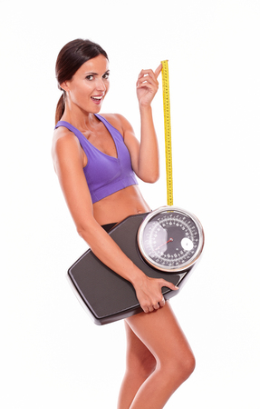 hair tied back: Healthy smiling brunette woman with a tape measure and a scale looking at camera while wearing violet and black gymnastic clothing, hair tied back, isolated Stock Photo