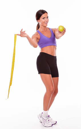 hair tied back: Healthy brunette woman with a tape measure and apple looking at camera while wearing violet and black gymnastic clothing, hair tied back, isolated Stock Photo