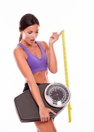 hair tied back: Healthy surprised brunette woman with a tape measure looking at a scale while wearing violet and black gymnastic clothing, hair tied back, isolated