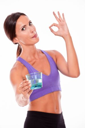 perfect sign: Healthy brunette woman offering a glass of water, gesturing perfect sign, looking at camera licking her lips while wearing violet and black gymnastic clothing, isolated Stock Photo