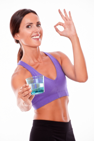 perfect sign: Healthy brunette woman offering a glass of water, gesturing perfect sign, looking at camera smiling while wearing violet and black gymnastic clothing, isolated Stock Photo