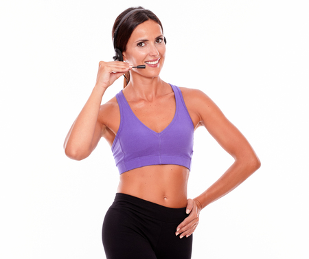 head phones: Healthy smiling brunette woman with head phones and microphone looking at camera, hand on hip while wearing violet and black gymnastic clothing on white background Stock Photo