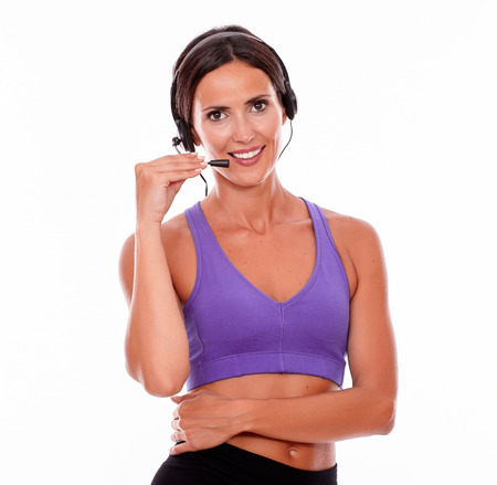 head phones: Healthy smiling brunette woman with head phones and microphone looking at camera, arm crossed while wearing violet and black gymnastic clothing on white background