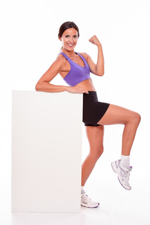 lifted: Healthy satisfied woman holding a blank placard fist in the air while looking at camera one foot lifted wearing violet and black gymnastic clothing, isolated Stock Photo