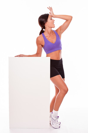 hand on forehead: Healthy surprised brunette woman holding blank placard and looking away with her hand on her forehead while wearing violet and black gymnastic clothing, isolated Stock Photo