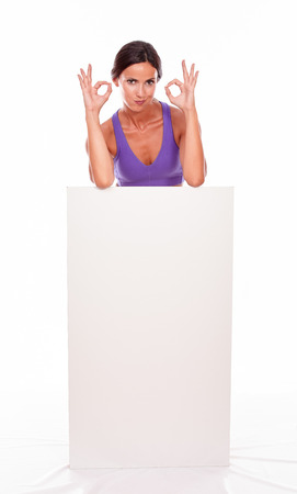 pouting: Healthy pouting brunette woman standing behind a blank placard gesturing thumbs up and looking at camera while wearing violet gymnastic clothing, isolated Stock Photo