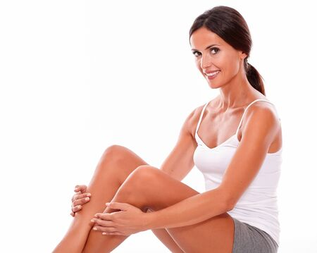 hair tied back: Attractive young woman smiling happily while looking at camera with her arms touching her calves wearing a white tank top and hair tied back, isolated