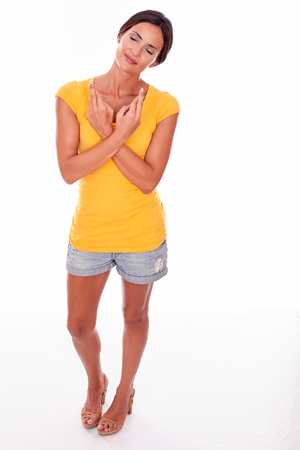 ojos cerrados: Deseando mujer morena haciendo un gesto con los dedos cruzados y los ojos cerrados llevaba una camiseta amarilla y pantalones vaqueros cortos aislado