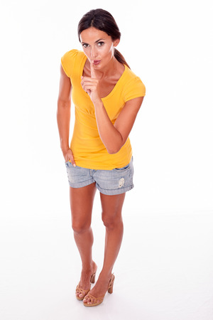secretive: Secretive brunette woman gesturing finger to her lips while looking at camera and wearing a yellow t-shirt and short jeans isolated