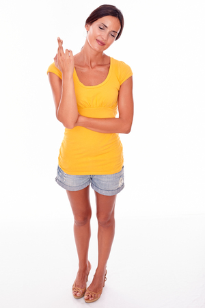 ojos cerrados: Wishing brunette woman gesturing crossed fingers with closed eyes and wearing a yellow t-shirt and short jeans isolated