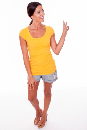 Happy smiling brunette woman gesturing a peace sign while looking away and wearing a yellow t-shirt and short jeans isolated Stock Photo