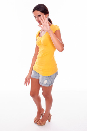 obscuring: Frowning brunette woman gesturing stop with her left hand obscuring her face while looking at camera and wearing a yellow t-shirt and short jeans isolated