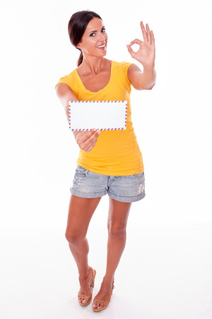 perfect sign: Smiling brunette woman gesturing a perfect sign with a blank envelope while looking at camera wearing a yellow t-shirt and short jeans isolated
