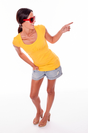fits in: Happy brunette pointing and looking to her left while wearing a yellow t-shirt, short jeans and red sunglasses on a white background