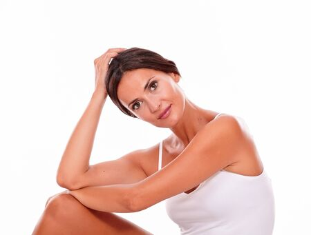 hair tied: Attractive woman with her knee up and her hand to head while looking at camera thoughtfully wearing a white tank top, hair tied back isolated Stock Photo