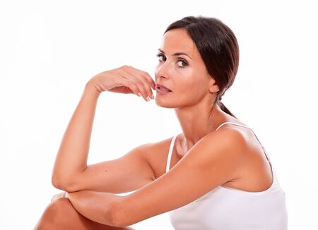 hair tied: Attractive woman with her knee up and her hand to face while looking at camera thoughtfully wearing a white tank top, hair tied back isolated