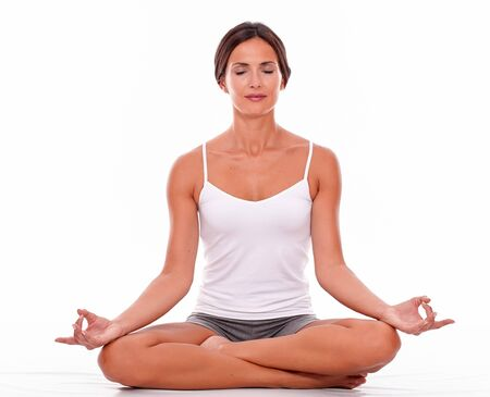 legs crossed on knee: Young brunette woman sitting with her legs crossed while meditating with closed eyes and wearing a white tank top and gray shorts isolated