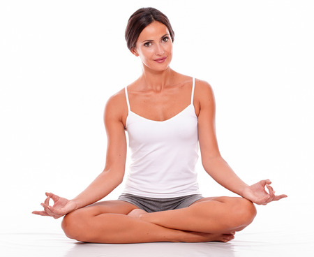 legs crossed on knee: Smiling young woman sitting with her legs crossed while looking at camera while wearing a white tank top and gray shorts isolated