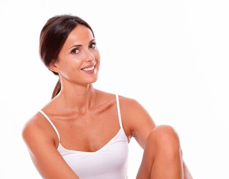 hair tied back: Attractive young woman smiling happily while looking at camera with her knee up while wearing a white tank top and hair tied back, isolated Stock Photo