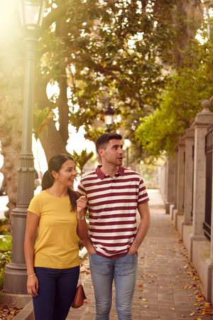 leisurely: Young couple strolling leisurely down a road sightseeing, smiling happily while dressed casually in jeans and t-shirts