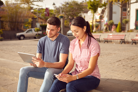 town square: Young couple sitting in a town square on a bench looking at a tablet and a cell phone while dressed casually in jeans and t-shirts Stock Photo