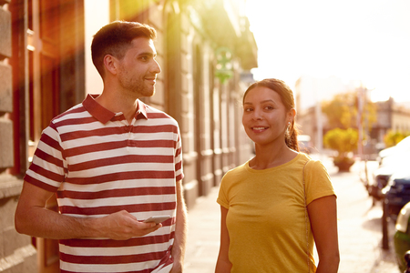 them: Young couple looking away talking and smiling happily while dressed casually in t-shirts with old buildings behind them