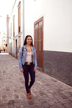 empedrado: Pretty young girl strolling down a narrow paved street with old gray and white buildings behind her in casual clothing
