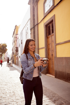 empedrado: Pretty young girl looking at a picture on her camera with the sun behind her in a street with old buildings behind her dressed casually