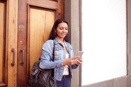 puertas de madera: chica muy joven que mira su teléfono celular con una sonrisa mientras se está en frente de las puertas de madera, con el cabello suelto en pantalones vaqueros y chaqueta