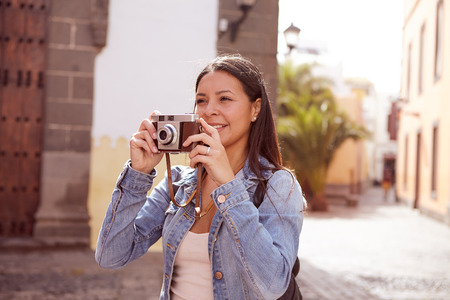 loose hair: Pretty young girl taking pictures, smiling with her camera wearing her long hair loose and casual clothing with a narrow street in her background