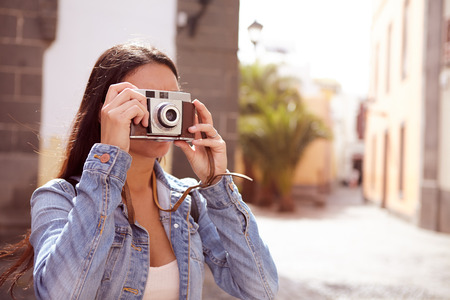Young brunette focusing to take a picture with her camera wearing her hair loose and casual clothing with a narrow street in her background